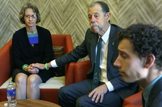 Mickey Redus, center, holds his wife Valerie Redus's hand, with their son Kris Redus at right, during an interview.  The parents of Robert Cameron Redus, the slain student at University of the Incarnate Word, were in federal court in San Antonio for a hearing to determine if a lawsuit filed by lawyers of Valerie Redus and Mickey Redus, should stay in federal court or be sent back to state court.  Monday, Nov. 17, 2014. Photo: BOB OWEN, San Antonio Express-News / © 2014 San Antonio Express-News