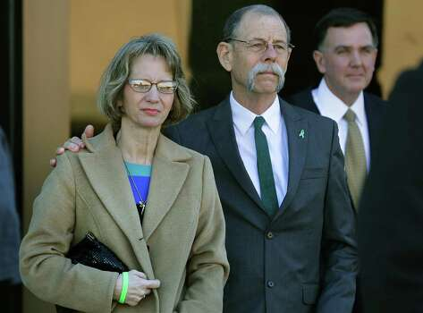 Valerie Redus, left, and her husband Mickey, emerge from the John Wood U.S. Courthouse with their lawyer Brent C. Perry, right.  The parents of Robert Cameron Redus, the slain student at University of the Incarnate Word, were in federal court in San Antonio for a hearing to determine if a lawsuit filed by lawyers of Valerie Redus and Mickey Redus, should stay in federal court or be sent back to state court.  Monday, Nov. 17, 2014. Photo: BOB OWEN, San Antonio Express-News / © 2014 San Antonio Express-News
