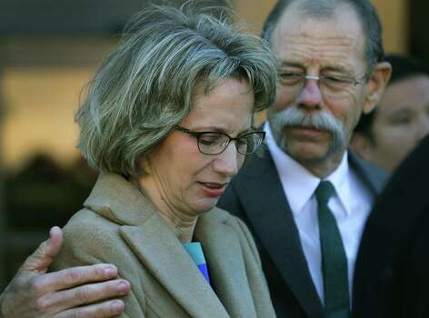 Valerie Redus, left, is comforted by her husband Mickey Redus, as they emerge from the John Wood U.S. Courthouse.  The parents of Robert Cameron Redus, the slain student at University of the Incarnate Word, were in federal court in San Antonio for a hearing to determine if a lawsuit filed by lawyers of Valerie Redus and Mickey Redus, should stay in federal court or be sent back to state court.  Monday, Nov. 17, 2014. Photo: BOB OWEN, San Antonio Express-News / © 2014 San Antonio Express-News