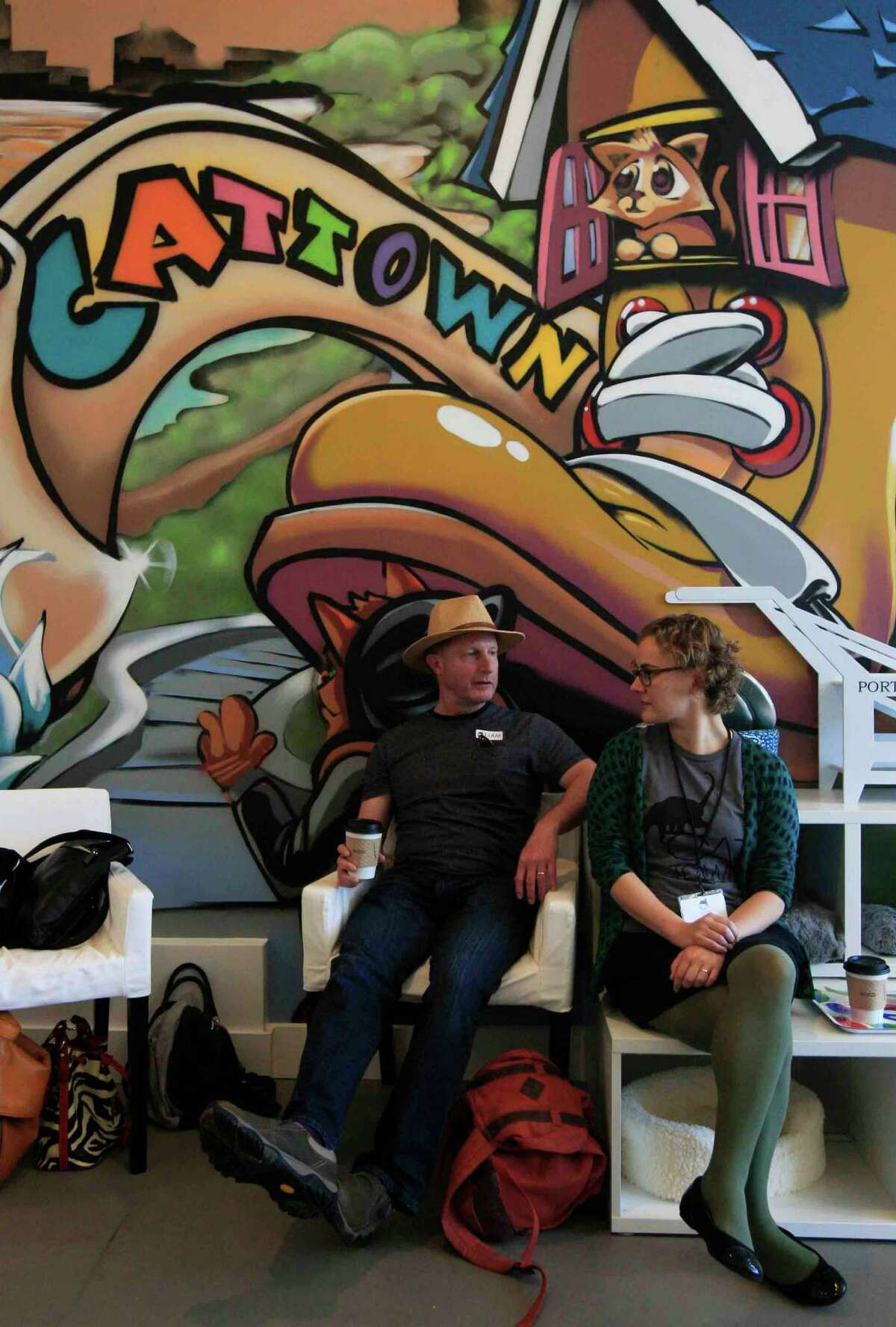 Volunteer Quinn White (right) of Berkeley chats with Andy Green of El Cerrito at the new Cat Town Cafe in Oakland.