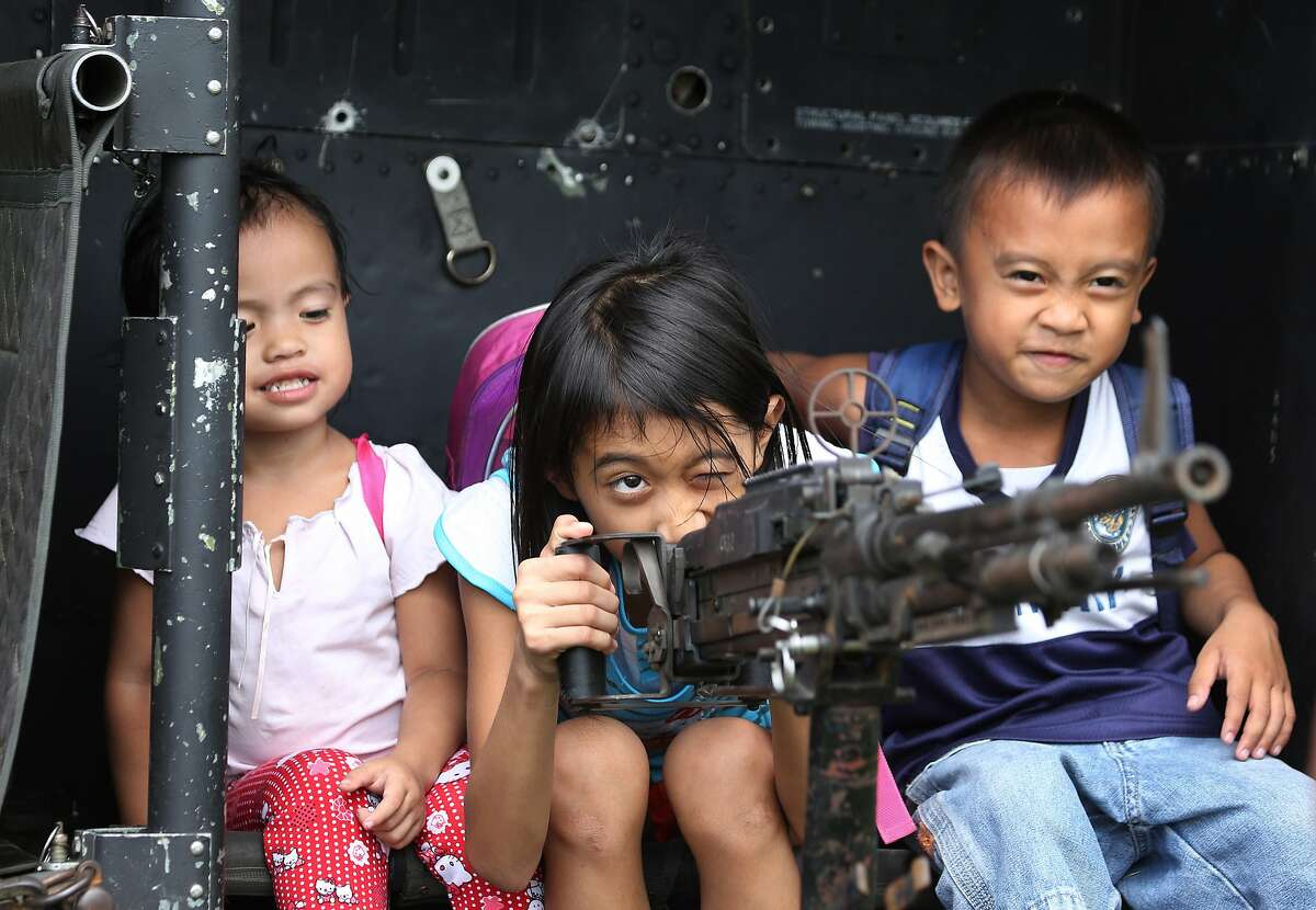 WE'VE DECIDED NOT TO DO OUR HOMEWORK. ANY OBJECTIONS? Filipino children play with a machine gun mounted on a UH-1H military helicopter during the 75th anniversary of the Philippine Defense Department at Camp Aguinaldo in suburban Quezon City.