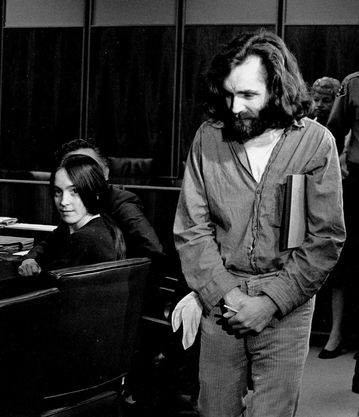 """FILE - In this Oct. 13,1970 file photo, cult leader Charles Manson walks into the courtroom as Susan Atkins, a member of his family of followers, looks on in Santa Monica, Calif. A marriage license has been issued for Manson to wed 26-year-old Afton Elaine Burton, who left her Midwestern home nine years ago and moved to Corcoran, California to be near him. Burton, who goes by the name """"Star,"""" told the AP that she and Manson will be married next month. (AP Photo/File)"""