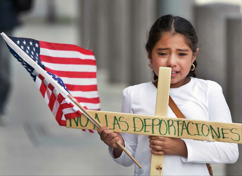 "Yesenia Del Carmen 8, carries a cross reading ""No to the Deportations,"" ""as she and her grandmother join an immigrant-rights supporters ""Procession of the Cross"" walk, led by U.S.-born children from the Federal building to the Cathedral of Our Lady of the Angels in Los Angeles, Friday, Apr. 18, 2014. (AP Photo/Damian Dovarganes) Photo: Damian Dovarganes, STF / AP"