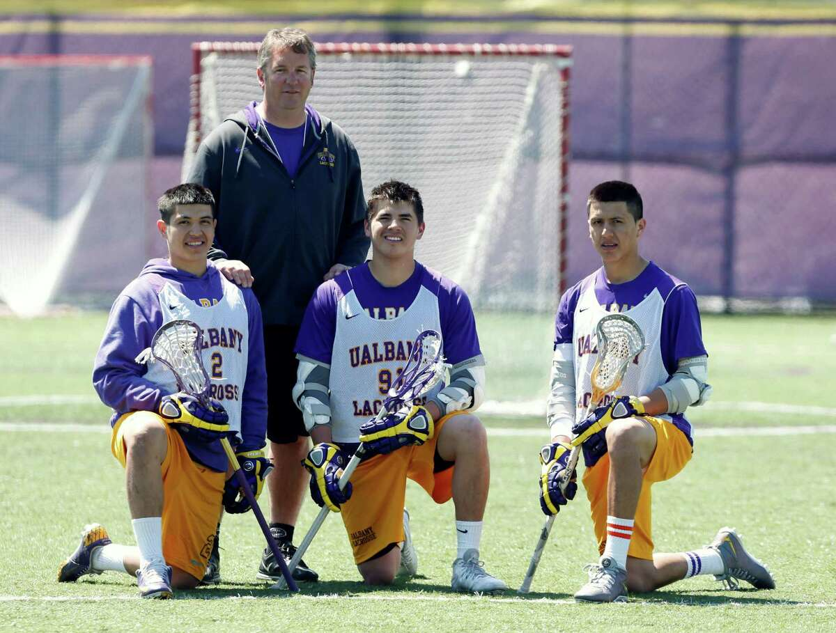 In this photo taken on Monday, April 28, 2014, University at Albany lacrosse players Miles Thompson (2), Ty Thompson (91) and Lyle Thompson (4) pose with coach Scott Marr after practice in Albany, N.Y. The trio of Native American players, Miles, younger brother Lyle, and cousin Ty, have transformed Albany into an offensive juggernaut in Division I men's lacrosse. (AP Photo/Mike Groll) ORG XMIT: NYMG205