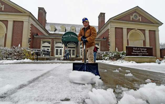 NYS Parks and Recreation Dept. worker Evaristo Valentine clears snow in front of the Hall of Springs Monday morning, Nov. 17, 2014, at Saratoga Spa State Park in Saratoga Springs, N.Y. (Skip Dickstein/Times Union) Photo: SKIP DICKSTEIN