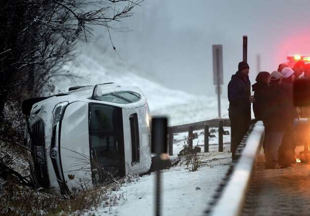 A car lays on its side at mile marker 22.1 in the  I-87 northbound lanes during a snow hampered rush hour Monday morning, Nov. 17, 2014, in Saratoga Springs, N.Y. (Skip Dickstein/Times Union) Photo: SKIP DICKSTEIN
