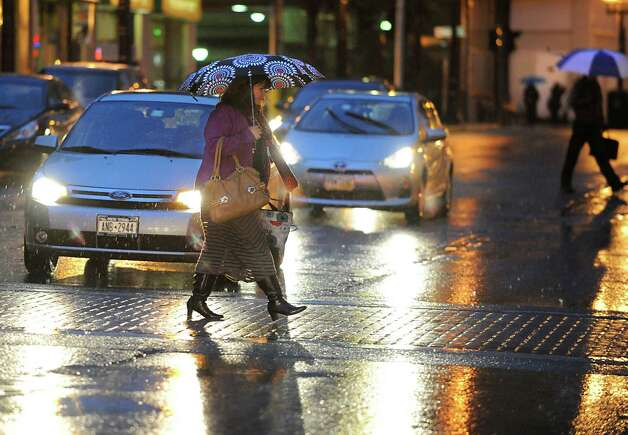 Pedestrians use umbrellas to shield the cold rain as they cross South Pearl St. on Monday, Nov. 17, 2014 in Albany, N.Y.  (Lori Van Buren / Times Union) Photo: Lori Van Buren