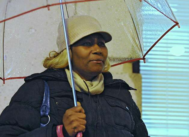 Marcia Payne of Albany uses an umbrella to shield herself from the cold rain as she waits for a bus on South Pearl St. on Monday evening, Nov. 17, 2014, in Albany, N.Y.  (Lori Van Buren / Times Union) Photo: Lori Van Buren