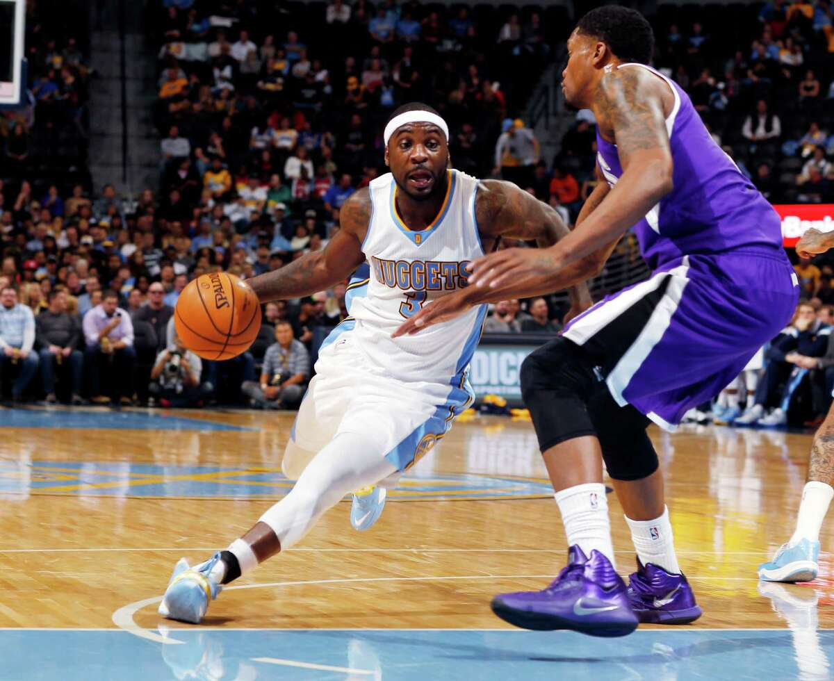 Denver Nuggets guard Ty Lawson, left, drives the lane for a shot as Sacramento Kings forward Rudy Gay covers in the third quarter of the Kings' 110-105 victory in an NBA basketball game in Denver on Monday, Nov. 3, 2014. (AP Photo/David Zalubowski)