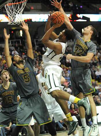 Siena's Lavon Long is guarded by Vermont's Hecto Harold, left, and Ethan O'Day as he drives to the basket during a basketball game at the Times Union Center on Monday, Nov. 17, 2014 in Albany, N.Y.  (Lori Van Buren / Times Union) Photo: Lori Van Buren / 00029488A