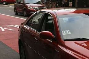 """A red sedan bears the distinctive """"U"""" logo from Uber. But is the driver an employee or contractor?"""