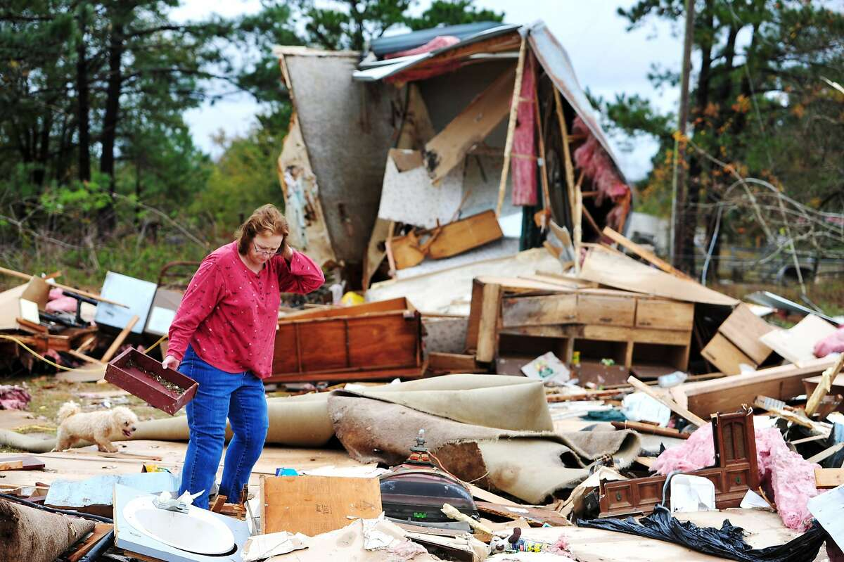 Sue Freeman looks through her destroyed mobile home for pieces of a child's roll top desk that was stored in it, Monday, Nov. 17, 2014, in Cochran, Ga. A tornado warning sent folks scrambling for shelter before 10 a.m. Monday morning in parts of Jones, Baldwin and Wilkinson counties, according to the Macon Telegraph Twiggs County Sheriff Chief Deputy Billy Boney said he thinks a tornado briefly touched down on the property at 2473 Longstreet Road, which has a Cochran address. \AP Photo/The Telegraph, Woody Marshall