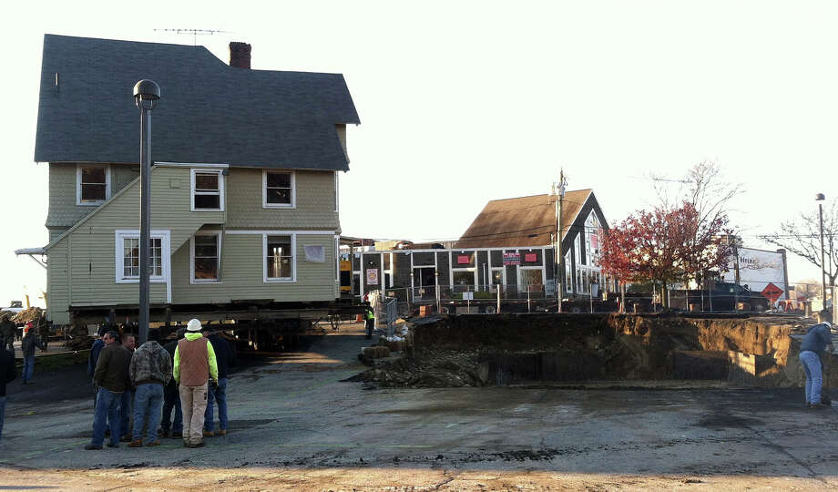 The Kemper-Gunn House is poised next to its new foundation in the Baldwin parking lot, after its move across Elm Street early Tuesday. Photo: Jarret Liotta / Westport News