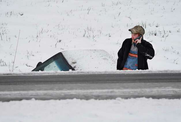 Caelan Slate, of Nortonville, Ky., calls to say he is going to be a little late to work after losing control and landing his truck in a ditch of off the Pennyrile Parkway in Henderson County, Monday, Nov. 17, 2014. The first winter storm of the season closed schools and made driving treacherous. Photo: Mike Lawrence, AP / The Gleaner