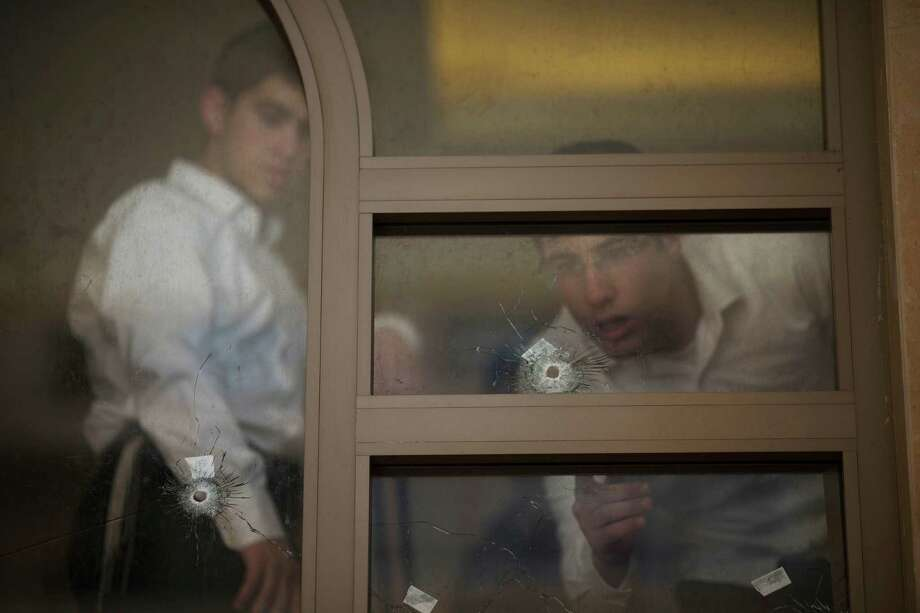 Two youths look at bullet holes and forensic evidence inside a synagogue after an attack in Jerusalem, Tuesday, Nov. 18, 2014. Two Palestinians stormed a Jerusalem synagogue on Tuesday, attacking worshippers praying inside with knives, axes and guns, and killing four people before they were killed in a shootout with police, officials said. Photo: Ariel Schalit, AP / AP