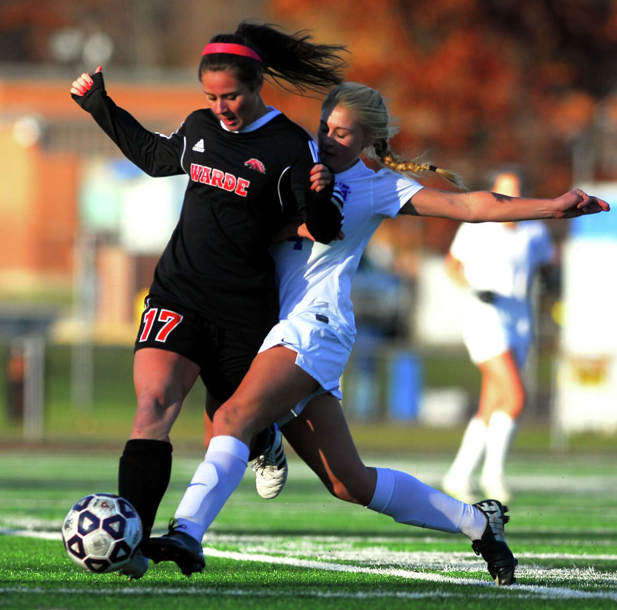 Warde's Alexa Montani (17) and Glastonbury's Taylor Walker battle for possession during the CIAC Class LL girls' soccer state championship at Ken Strong Stadium in West Haven on November 15. The Mustangs lost 2-1 in double overtime.