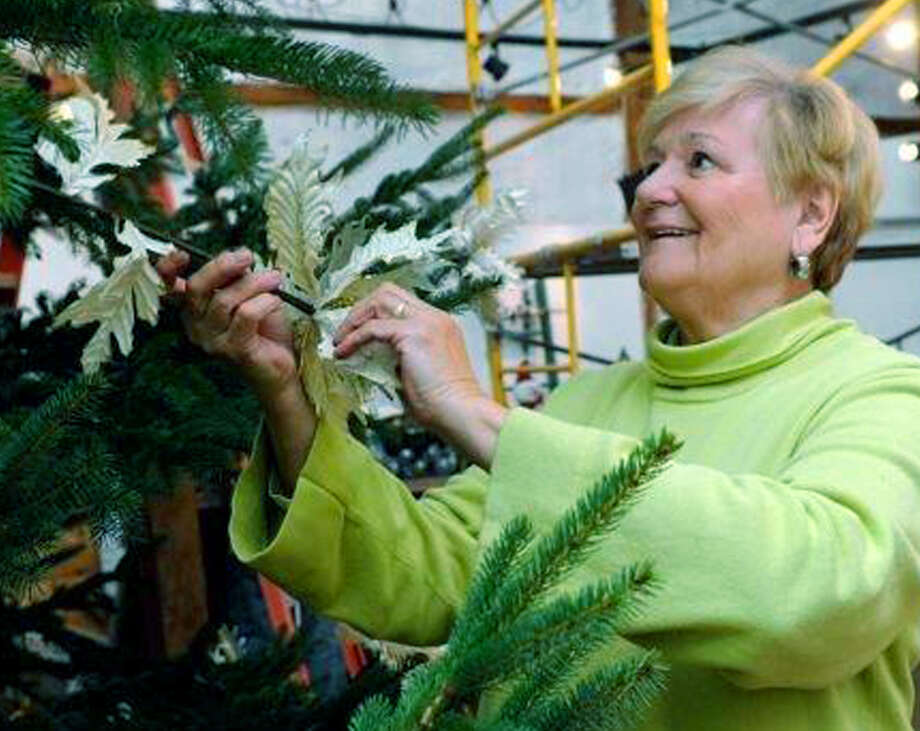 Helen Cherney of New Milford employs her decorating skills to help trim the 27-foot spruce tree now gracing the Silo for its holiday events. November 2014 Photo: Carol Kaliff / The News-Times