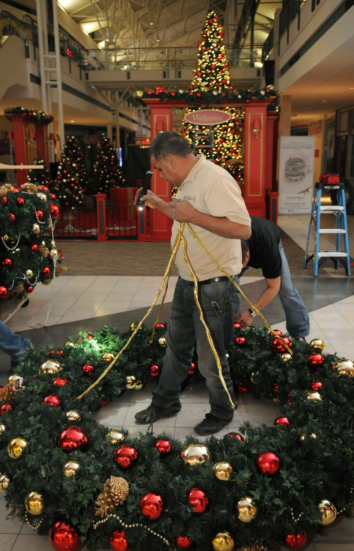 Walter Andino of Always in Season leads his team in their hanging of wreath chandeliers during seasonal decorating of The Woodlands Mall on Nov. 5.