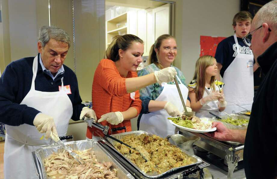 Volunteer servers fill plates with roast turkey and all the fixins during the the 2012 Community Thanksgiving Day Feast. Volunteers are still needed for this year's free, ecumenical feast, which is expected to attract more than 300 diners. Photo: Lindsay Niegelberg / Stamford Advocate