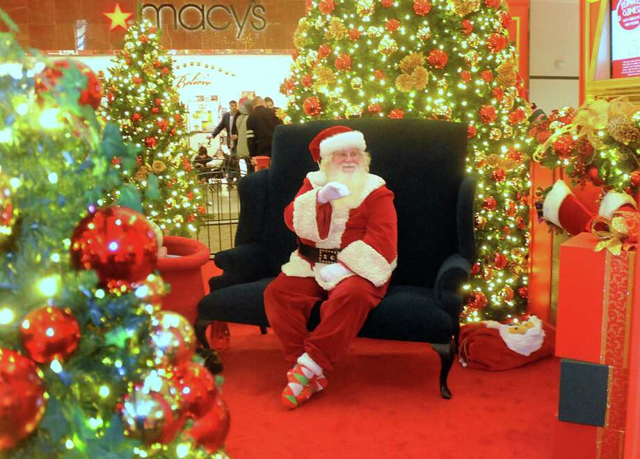 Santa Claus waves to children at The Woodlands Mall in 2013. This year, Santa's taking online reservations at The Woodlands and 11 other Houston-area malls.  Photo: David Hopper, Freelance / freelance
