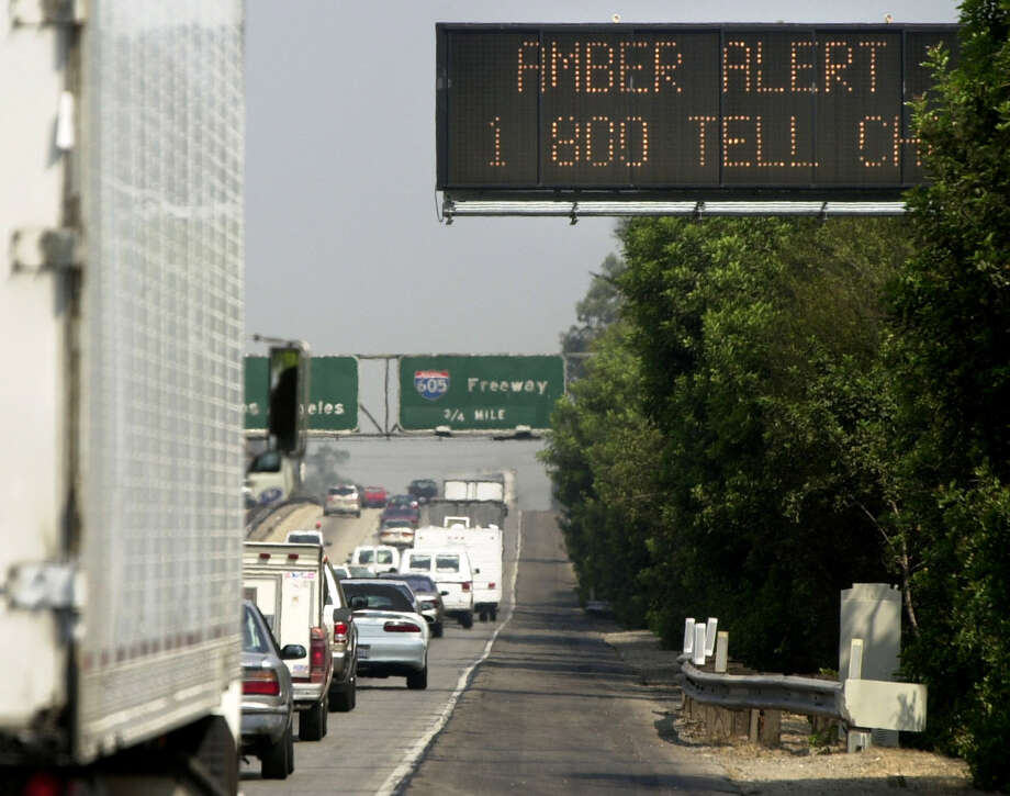 Motorists traveling northbound on Interstate-5 near Florence Avenue in Norwalk, Calif., are notified through the state-wide Amber Alert System, top right, of a suspect vehicle involved in a kidnapping in the Antelope Valley, Thursday morning, Aug. 1, 2002. Two teen-age girls abducted at gunpoint early Thursday were rescued 100 miles away after their kidnapper crashed his getaway car and was shot to death by sheriff's deputies, authorities said. (AP Photo/Whittier Daily News, Keith Durflinger) Photo: KEITH DURFLINGER / KEITH DURFLINGER / AP / WHITTIER DAILY NEWS