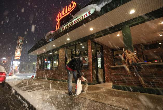 Jesse Braun salts the sidewalks infront of Julie's Pizzeria on Monday, Nov. 17, 2014. Upstate New York is getting hit with a wintry mix of weather as the work week begins, with a foot of snow possible in some parts of the Adirondacks and lake-effect snow belts. About an inch of snow has fallen in areas north of Albany early Monday morning, while places closer to the city are getting a mix of sleet and rain.  (AP Photo/The Buffalo News, Harry Scull Jr.) ORG XMIT: NYBUE101 Photo: Harry Scull Jr., AP / The Buffalo News