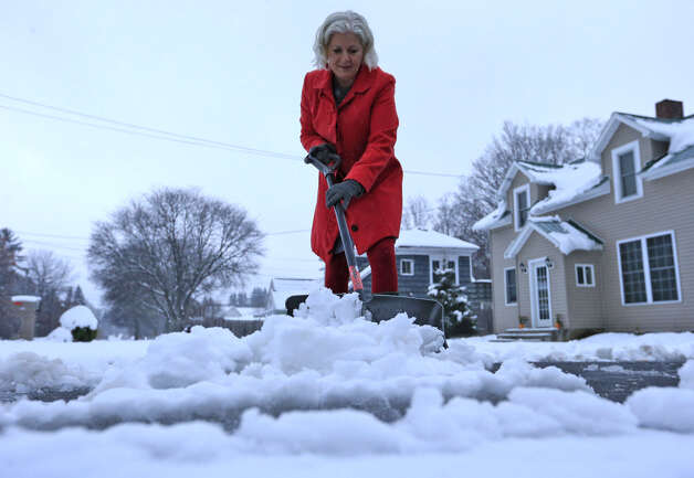 Lynette Johnson moves snow in front of her Mill Street home in Springville, NY on Monday, Nov. 17, 2014. Upstate New York is getting hit with a wintry mix of weather as the work week begins, with a foot of snow possible in some parts of the Adirondacks and lake-effect snow belts. About an inch of snow has fallen in areas north of Albany early Monday morning, while places closer to the city are getting a mix of sleet and rain. (AP Photo/The Buffalo News, Harry Scull Jr.) ORG XMIT: NYBUE104 Photo: Harry Scull Jr., AP / The Buffalo News
