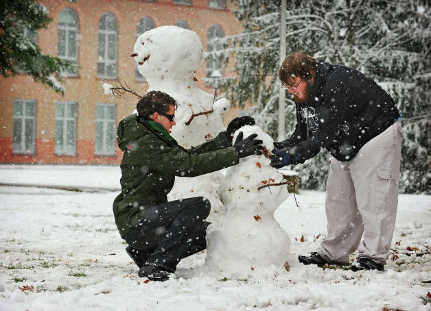 Clarkson University students, sophomore David B. Josephs, left, of Potsdam and freshman Dallas J. Blowers, of Watertown build a snowman at Clarkson University in Potsdam, N.Y., Monday, Nov. 17, 2014. More than a month before the arrival of winter, forecasters said snow off the Great Lakes could fall through Wednesday afternoon at a rate of five inches per hour in spots, and that wind gusts of up to 45 mph had the potential to make travel nearly impossible along sections of the New York State Thruway and Interstate 81. (AP Photo/ Watertown Daily Times, Jason Hunter) MANDATORY CREDIT ORG XMIT: NYWAT101 Photo: Jason Hunter, AP / Watertown Daily Times