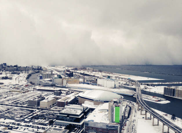 A band of storm clouds moves across Lake Erie and into Buffalo, N.Y., Tuesday, Nov. 18, 2014. Parts of New York measured the season's first big snowfall in feet, rather than inches, on Tuesday as 3 feet of lake-effect snow blanketed the Buffalo area and forced the closure of a 132-mile stretch of the state Thruway. (AP Photo/Gary Wiepert) ORG XMIT: NYR102 Photo: Gary Wiepert, AP / APfre170498