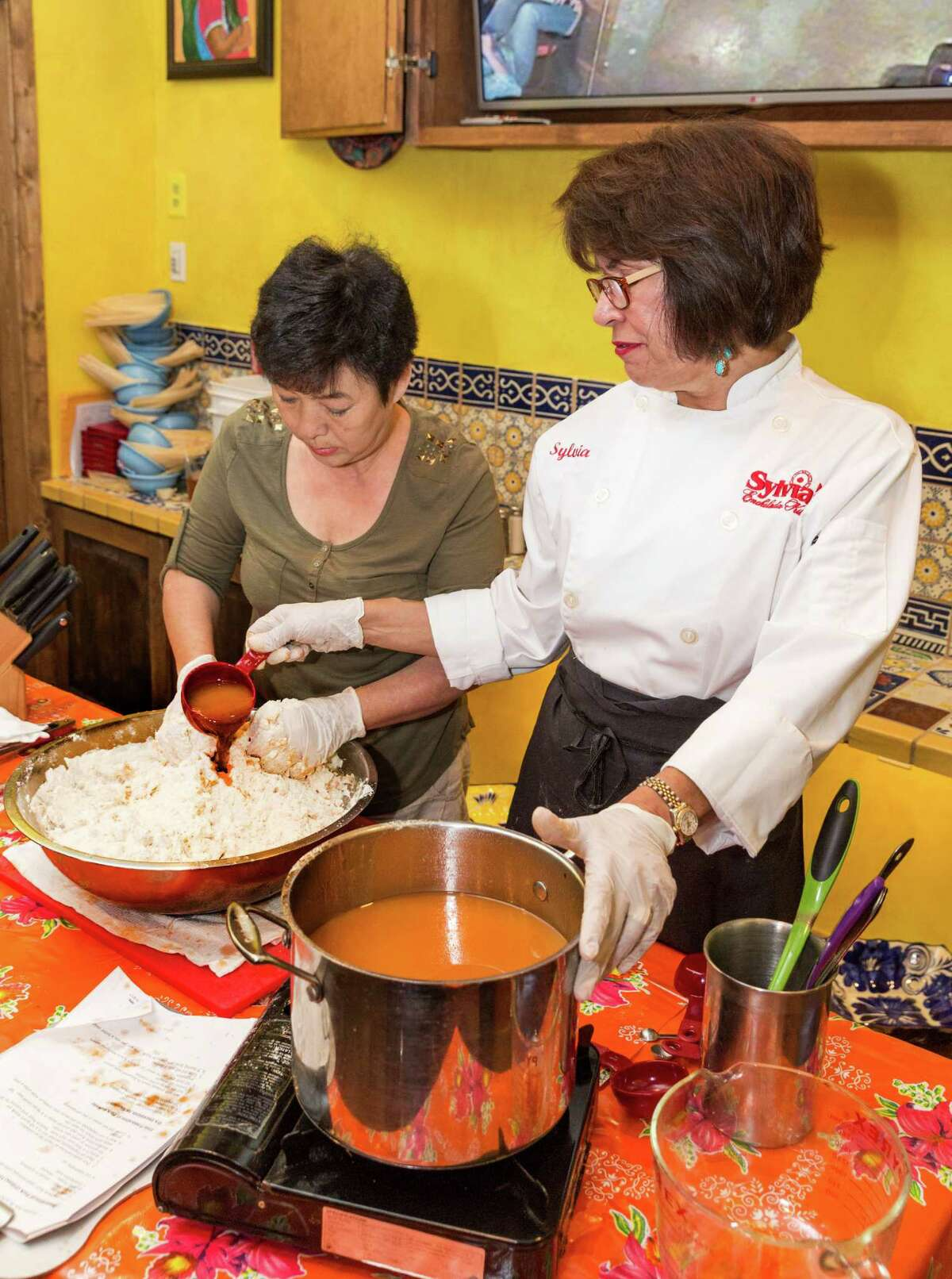 Sylvia Casares, owner of Sylvia's and Sylvia's Enchilada Kitchen restaurants, conducts a tamale-making class at her new restaurant Sylvia's, 1140 Eldridge Parkway. Classmember Suk Yi helps mix the Maseca mixture as Casares slowly adds the stock. Sylvia Casares, owner of Sylvia's and Sylvia's Enchilada Kitchen restaurants, conducts a tamale-making class at her new restaurant Sylvia's, 1140 Eldridge Parkway. Classmember Suk Yi helps mix the Maseca mixture as Casares slowly adds the stock.