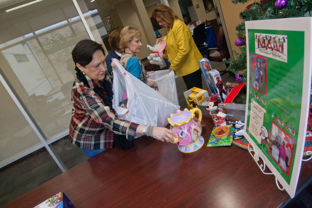 Volunteer Rosalie Solis Sharkey bags toys for storage before Memorial Assistance Ministries annual Christmas toy drive. Behind, volunteer Patty McLain, left, and Sandy Staffeld, senior director of resource development, also bag toys. Volunteer Rosalie Solis Sharkey bags toys for storage before Memorial Assistance Ministries annual Christmas toy drive. Behind, volunteer Patty McLain, left, and Sandy Staffeld, senior director of resource development, also bag toys.