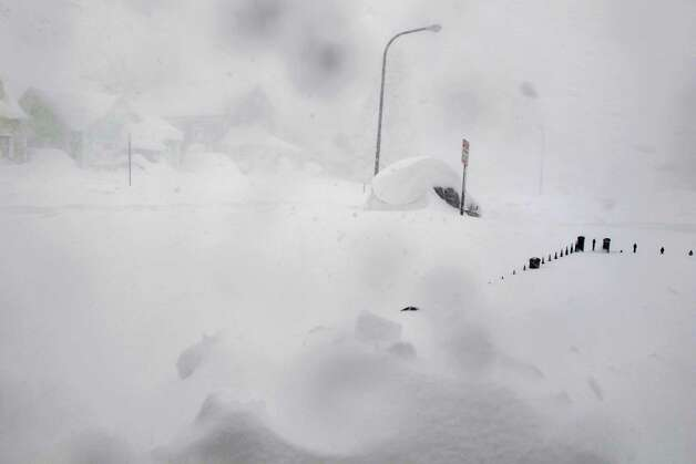 A 4-foot fence and SUV are nearly buried along a street in Buffalo, N.Y. on Tuesday, Nov. 18, 2014.  Parts of New York measured the season's first big snowfall in feet, rather than inches,  as 3 feet of lake-effect snow blanketed the Buffalo area.  The Thruway Authority said white-out conditions caused by wind gusts of more than 30 mph forced the closure of Interstate 90 in both directions from the Rochester area to Ripley, on the Pennsylvania border 60 miles southwest of Buffalo.  (AP Photo/Carolyn Thompson)  ORG XMIT: RPCT105 Photo: Carolyn Thompson, AP / ap