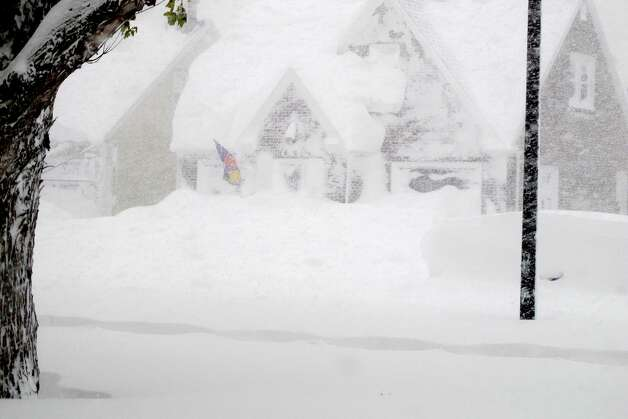 A house is obscured by wind-blown, lake-effect snow on Tuesday, Nov. 18, 2014 in Buffalo, N.Y. Parts of New York measured the season's first big snowfall in feet, rather than inches,  as 3 feet of lake-effect snow blanketed the Buffalo area.  The Thruway Authority said white-out conditions caused by wind gusts of more than 30 mph forced the closure of Interstate 90 in both directions from the Rochester area to Ripley, on the Pennsylvania border 60 miles southwest of Buffalo.  (AP Photo/Carolyn Thompson)  ORG XMIT: RPCT104 Photo: Carolyn Thompson, AP / ap