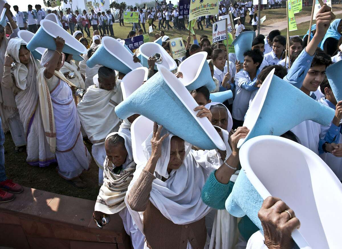 FLUSH MOB: Indian women carry toilets on their heads during the opening ceremony of the three-day International Toilet Festival in New Delhi. UNICEF estimates that almost 594 million - or nearly 50 percent of India's population - have no indoor plumbing or even outhouses, with the situation acute in dirt-poor rural areas.