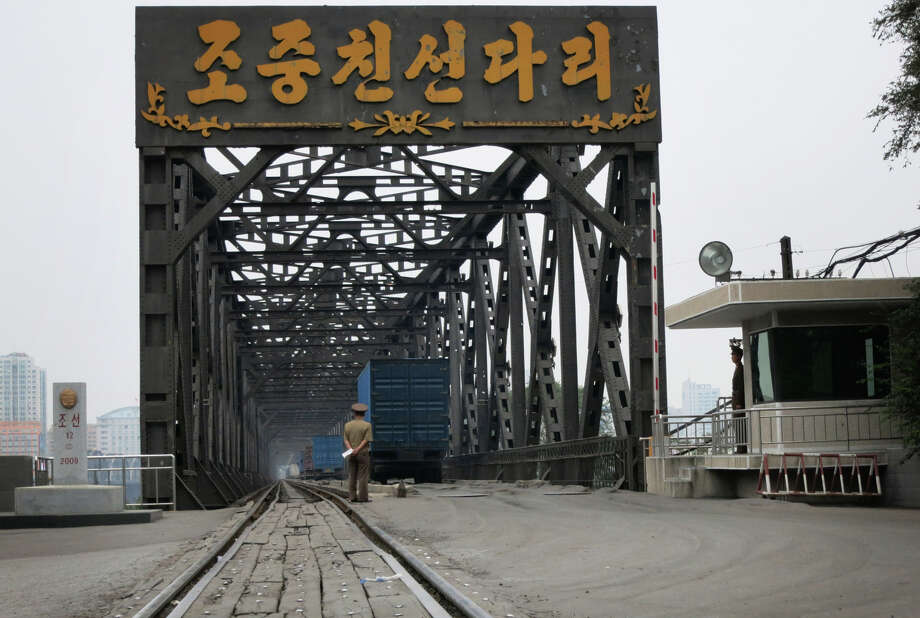 "Letters reading ""Korea China Friendship Bridge"" appear over the entrance to the incomplete bridge over the Yalu River in Sinuiju, North Korea. China has spent $350 million on the bridge. Photo: Associated Press / APTN"
