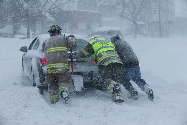 Firefighters from West End Hose Company in Depew, N.Y. help a stuck motorist on Transit Road, Tuesday, Nov. 18, 2014.  Several feet of lake-effect snow paralyzed the Buffalo area Tuesday, forcing state troopers to deliver blankets and other supplies to motorists stranded on the New York State Thruway and adding an ominous note to a wintry season that's already snarling travel and numbing fingers from the Midwest to the Carolinas.  (AP Photo/The Buffalo News, Derek Gee)  ORG XMIT: NYBUE102 Photo: Derek Gee, AP / The Buffalo News