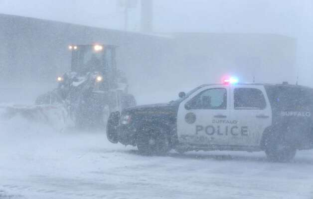 Buffalo Police block traffic on Bailey Avenue at the intersection with Clinton Street as heavy equipment clears snow, Tuesday, Nov. 18, 2014.   Several feet of lake-effect snow paralyzed the Buffalo area Tuesday, forcing state troopers to deliver blankets and other supplies to motorists stranded on the New York State Thruway and adding an ominous note to a wintry season that's already snarling travel and numbing fingers from the Midwest to the Carolinas.  (AP Photo/The Buffalo News, Derek Gee)  ORG XMIT: NYBUE104 Photo: Derek Gee, AP / The Buffalo News