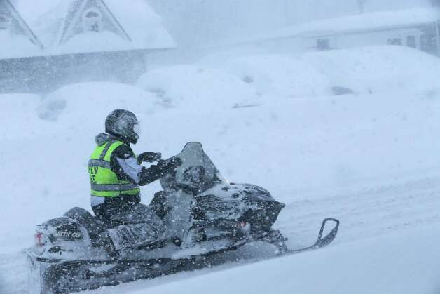 A Depew firefighter uses a snowmobile to travel down Transit Road, Tuesday, Nov. 18, 2014. Several feet of lake-effect snow paralyzed the Buffalo area Tuesday, forcing state troopers to deliver blankets and other supplies to motorists stranded on the New York State Thruway and adding an ominous note to a wintry season that's already snarling travel and numbing fingers from the Midwest to the Carolinas.  (AP Photo/The Buffalo News, Derek Gee)  ORG XMIT: NYBUE103 Photo: Derek Gee, AP / The Buffalo News