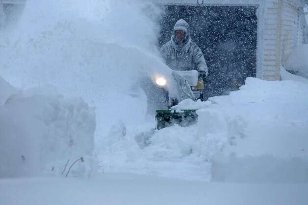 Jerry Delzer attempts to clear the snow in his driveway in Depew, N.Y. on Tuesday, Nov. 18, 2014.  Several feet of lake-effect snow paralyzed the Buffalo area Tuesday, forcing state troopers to deliver blankets and other supplies to motorists stranded on the New York State Thruway and adding an ominous note to a wintry season that's already snarling travel and numbing fingers from the Midwest to the Carolinas.  (AP Photo/The Buffalo News, Derek Gee)  ORG XMIT: NYBUE101 Photo: Derek Gee, AP / The Buffalo News