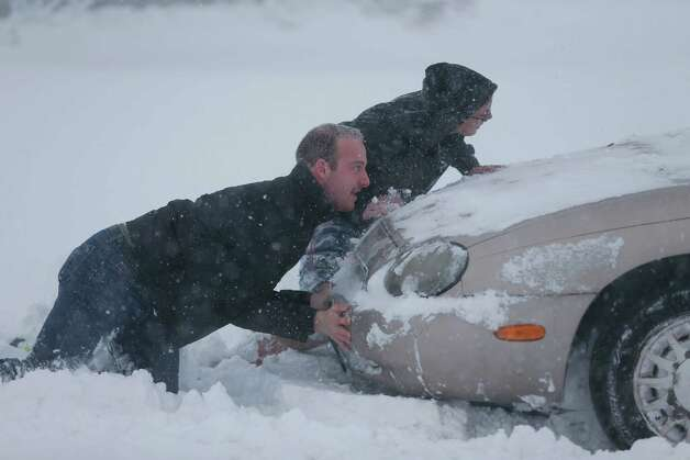 Eric Dehond, left, and Dakota Paciorkowski help push out a stuck motorist on George Urban Boulevard in Depew, N.Y. on Tuesday, Nov. 18, 2014.  Several feet of lake-effect snow paralyzed the Buffalo area Tuesday, forcing state troopers to deliver blankets and other supplies to motorists stranded on the New York State Thruway and adding an ominous note to a wintry season that's already snarling travel and numbing fingers from the Midwest to the Carolinas.  (AP Photo/The Buffalo News, Derek Gee)  ORG XMIT: NYBUE105 Photo: Derek Gee, AP / The Buffalo News