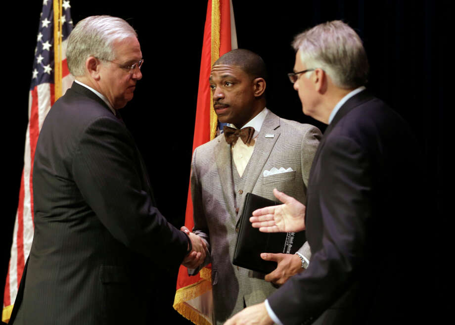 Missouri Gov. Jay Nixon (left) swears in the Rev. Starsky Wilson and Rich McClure as co-chairs of a commission. Photo: Jeff Roberson / Associated Press / AP