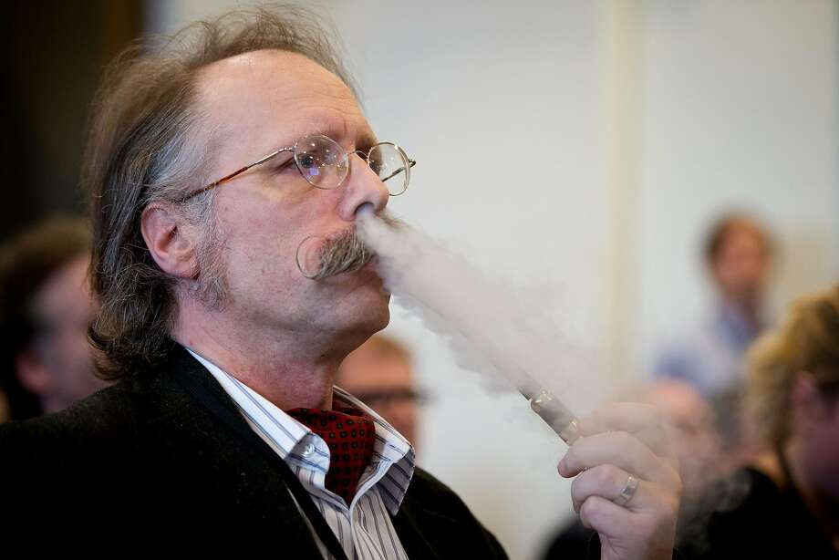 "A file picture taken on November 12, 2013, shows a delegate using an e-pipe during ""The E-Cigarette Summit"" in London. Oxford Dictionaries picked ""vape"" -- the act of smoking an e-cigarette -- as their new word of the year on Tuesday November 18, 2014, with the affectionate ""bae"" and the more pragmatic ""contactless"" as runners-up. Photo: Leon Neal, AFP/Getty Images"