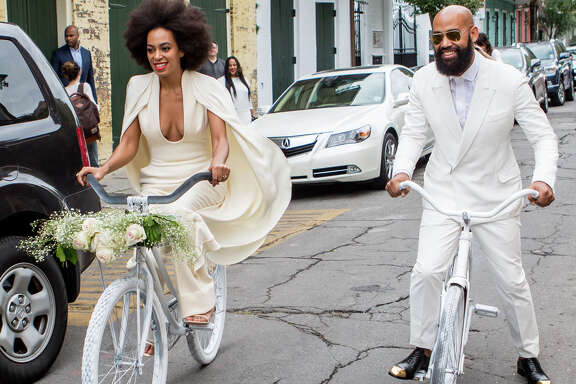 Solange Knowles (wearing a pre-ceremony ensemble by Stephane Rolland) and her fiance, music video director Alan Ferguson, ride bicycles on the streets of the French Quarter en route to their wedding ceremony at the Marigny Opera House on November 16, 2014 in New Orleans, Louisiana.  (Photo by Josh Brasted Getty/WireImage)