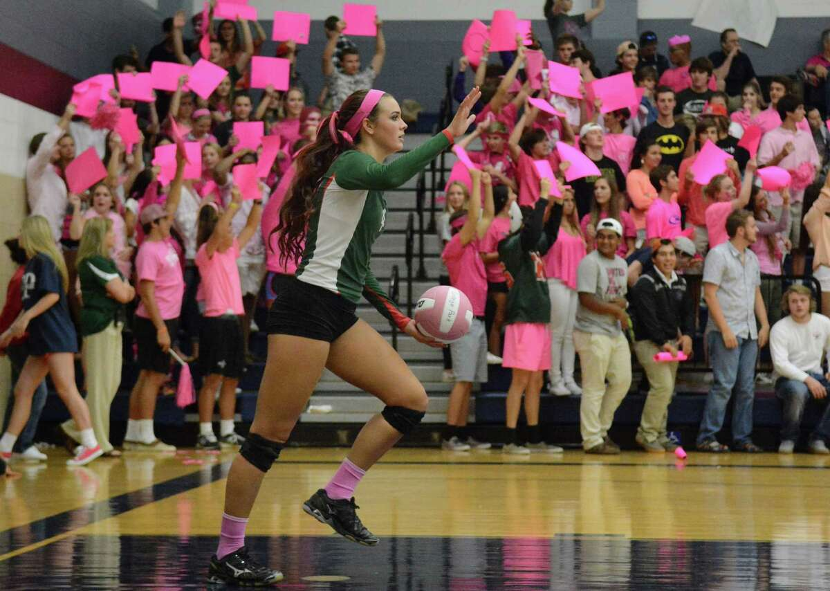 Lady Highlander senior setter Kendall Cook serves in front of the pink-clad placard-carrying student section during the annual Dig Pink match between The Woodlands and Colleg Park High Schools at TWCP on Oct. 14.