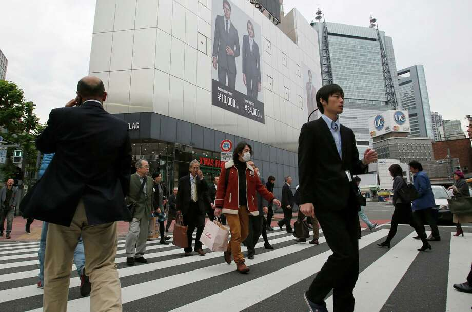 People walk on a pedestrian crossing in Tokyo Monday, Nov. 17, 2014. Japan's economy unexpectedly slid into recession as housing and business investment declined following a sales tax hike, further clouding the outlook for the global economy. (AP Photo/Shizuo Kambayashi) Photo: Shizuo Kambayashi / Associated Press / AP