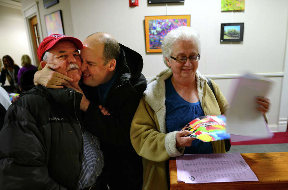 "John Drmic reaches to hug his father John, left, as John's mom Anna checks out the Kennedy Center Calendar released at the ""2015 Unique Perspective"" calendar reception, cocktail hour, and awards presentation held at the Gallery@999 inside the Margaret E. Morton Government Center in downtown Bridgeport, Conn., on Tuesday Nov. 18, 2014. In its 30th year, the Kennedy Center calendar brightens the holidays with its artwork and at the same time brings joy the the talented artists who are recognized at this event. Photo: Christian Abraham / Connecticut Post"
