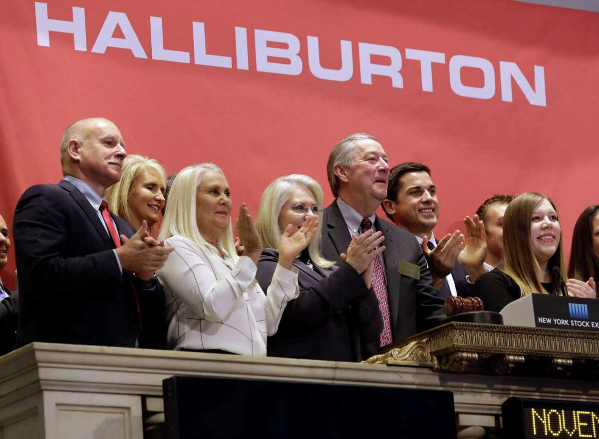 Halliburton Chairman, President and CEO David Lesar, third from right, rings the New York Stock Exchange opening bell, Tuesday, Nov. 18, 2014. In a deal that shows just how quickly falling prices can upend the energy industry, Halliburton is buying rival oilfield services company Baker Hughes for cash and stock worth $34.6 billion. (AP Photo/Richard Drew)