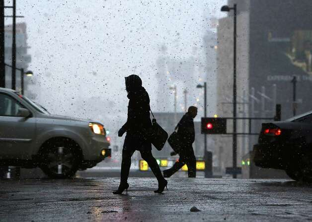 Pedestrians make their way through downtown Cincinnati, Monday morning, Nov. 17, 2014, as the season's first snowfall resulted in thousands of power outages in the Cincinnati area. The National Weather Service reported accumulations of 2 to 4 inches of snow in northern and central Ohio by Monday morning, while the southwest section of the state got 3 to 5 inches. (AP Photo/The Cincinnati Enquirer, Carrie Cochran) MANDATORY CREDIT;  NO SALES   ORG XMIT: OHCIN101 Photo: Carrie Cochran / The Cincinnati Enquirer