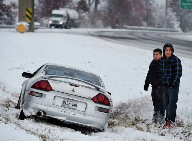 Stranded on the median, Angel Abendano, left, and Santiago Cuevas wait for assistance after losing control of their vehicle on the Pennyrile Parkway Monday, Nov. 17, 2014 after the first snow storm of the season dropped upwards of 5 inches of snow and ice on the area, closing schools. (AP Photo/The Gleaner, Mike Lawrence)  ORG XMIT: KYHEN102 Photo: Mike Lawrence / The Gleaner