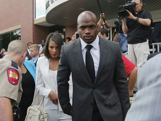 FILE - In this Oct. 8, 2014, file photo, Minnesota Vikings running back Adrian Peterson leaves court accompanied by his wife, Ashley Brown Peterson, in Conroe, Texas. The NFL suspended Adrian Peterson without pay for at least the remainder of the season. The league said Tuesday, Nov. 18, 2014, it informed the Minnesota Vikings running back he will not be considered for reinstatement before April 15 for violating the NFL personal conduct policy. (AP Photo/Houston Chronicle, Billy Smith II, File) ORG XMIT: TXHOU201 Photo: Billy Smith II / Houston Chronicle